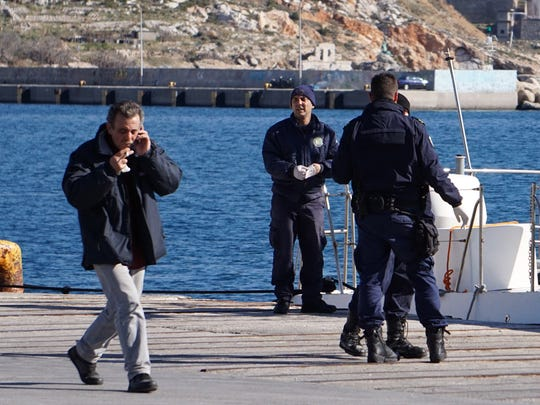 A man walks past Greek Coast guard officers standing near their vessel at the port of Kalymnos island on Friday, Jan. 22, 2016.