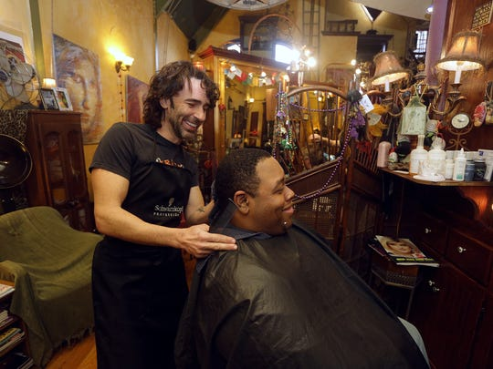 Tony Venute, owner of Mojo Pie Salon and Spa, left, cuts the hair of Isiah Washington. Stylists at Mojo Pie Spa and Salon treated area homeless to haircuts Monday, Jan. 25.
