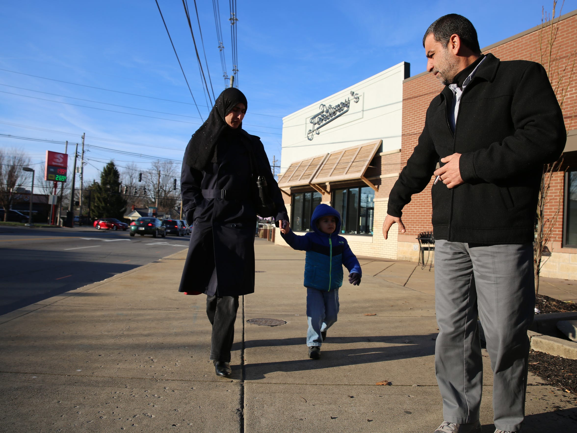 Ahmad Al Tybawi, his wife and youngest son walk from a bus stop in the Highlands to Kentucky Refugee Ministries for daily classes.