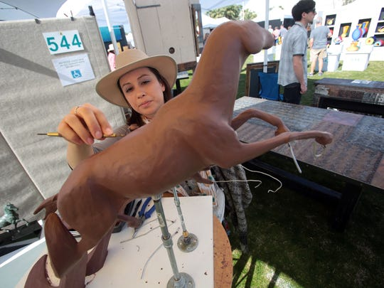 Rancho Cucamonga artist Deanna Rae with one of her  sculptures on Saturday, January 30, 2016 during the Southwest Arts Festival in Indio.