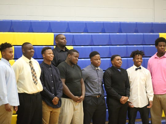 Rickards coach Quintin Lewis (back) stands with his eight football signees.