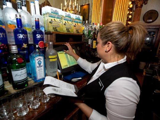 Manager and bartender Seneca Reyna rings up a check behind the bar at the Double Eagle restaurant and bar in Mesilla, February 2016.