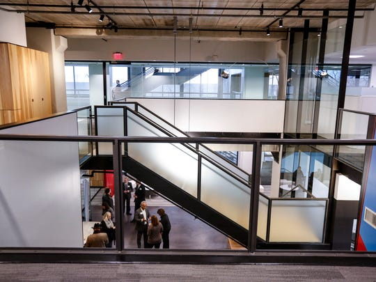 The office features an industrial design with bare concrete ceilings, exposed light fixtures and sprinklers.