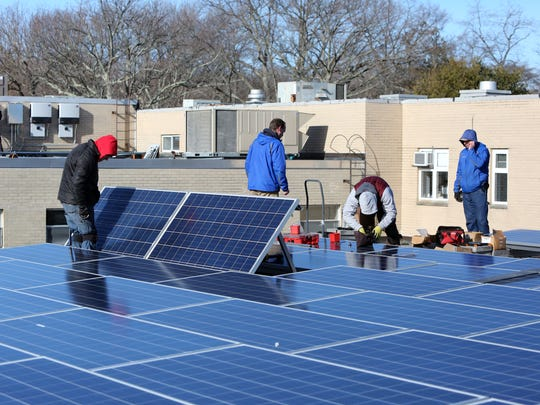 SunBlue Energy, a Sleepy Hollow based company, installs solar panels on the roof of a Westchester Day School building in Mamaroneck.