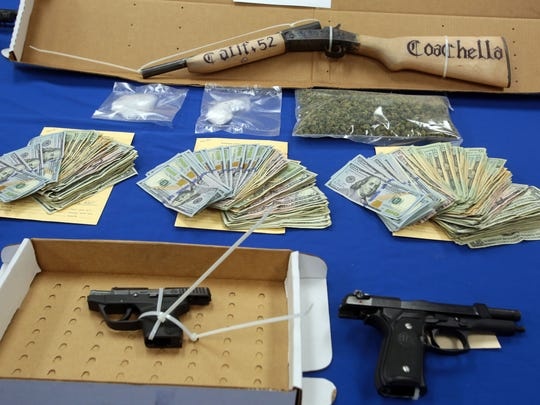 Weapons, money and drugs seized during today multi agency gang raid in Coachella on Thursday, February 25, 2016. Photo taken at the Riverside County Sheriff's Station in Thermal.