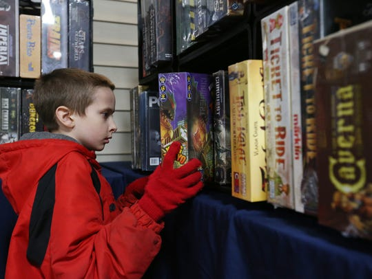 Brenton Dow, 11, of Two Rivers, checks out board games