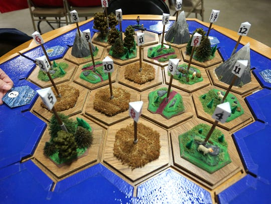 """Jerome Sinkovec sets up the handcrafted wooden 3D """"Settlers"""