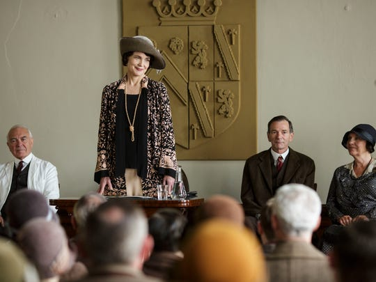 Cora (Elizabeth McGovern), standing, presides at a