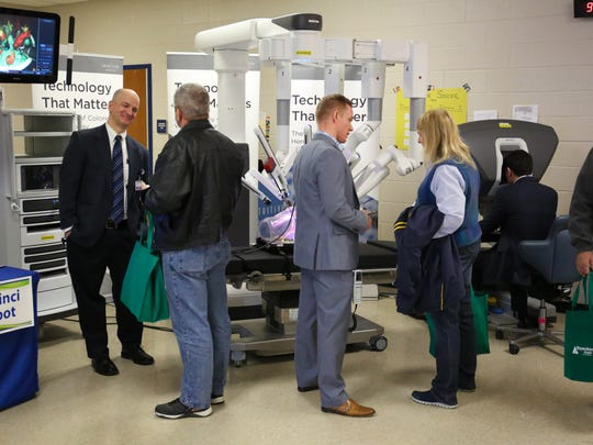 Dr. Shaun Bryant, far left, talks to attendees at the Waynesboro Hospital Health Fair about the da Vinci Si Surgical Robot.