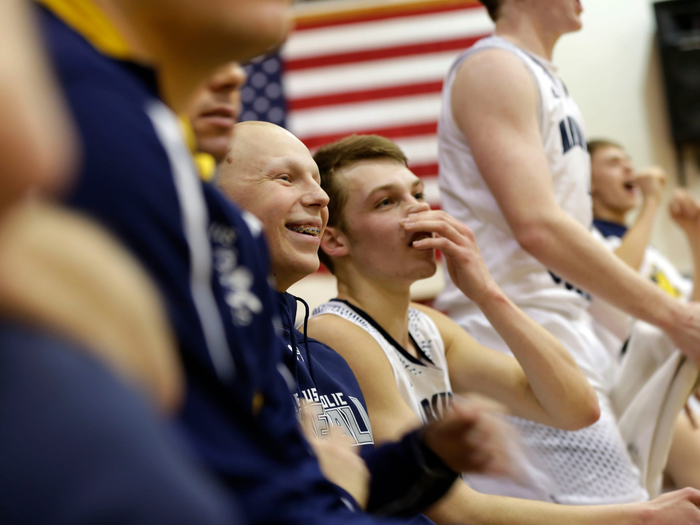 "Ryan Dieringer laughs while his teammates on the bench cheer on their ensuing victory over Athens at the home game March 1, 2016. 17 chemotherapy sessions later, Dieringer was on the bench with his team for the first time in nearly one year after his battle with cancer ended with ""no evidence of disease."""