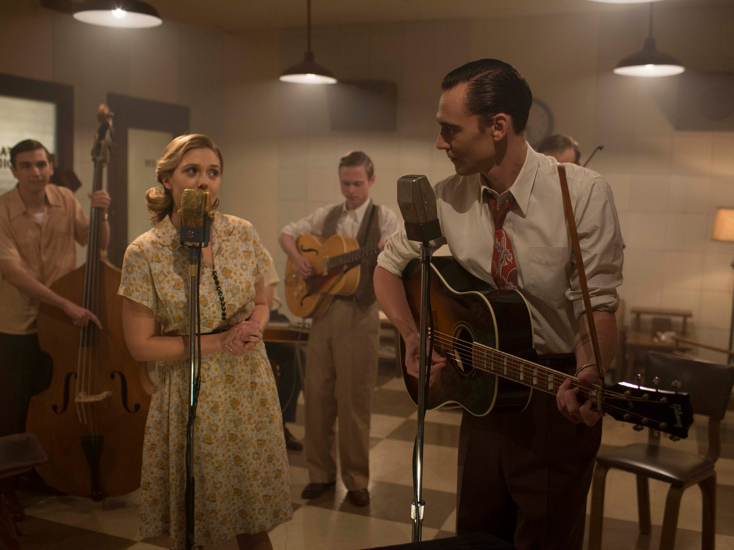 "Left to right: Elizabeth Olsen as Audrey Williams and Tom Hiddleston as Hank Williams sing along with the band in ""I Saw the Light."" The recording studio was built inside the  Petroleum Club in downtown Shreveport. At the time, the building was being renovated, so the film crew built the entire room, including the walls to shoot the scene, said location manager Ed Lipscomb."