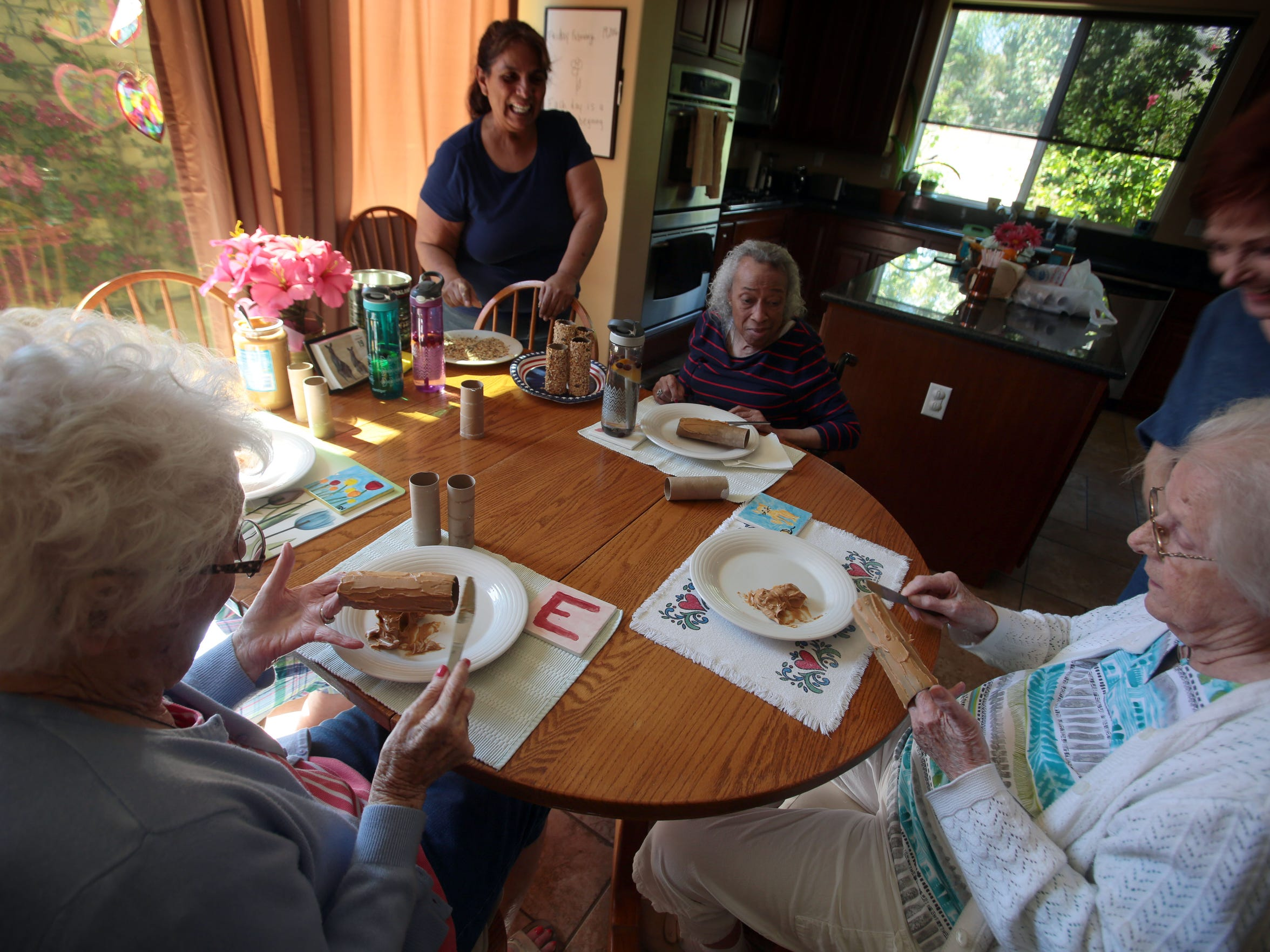 Seniors smear peanut butter on toilet paper rolls to make  bird feeders, one of several daily activities for them, in an assisted living facility in La Quinta on Friday, February 19, 2016.