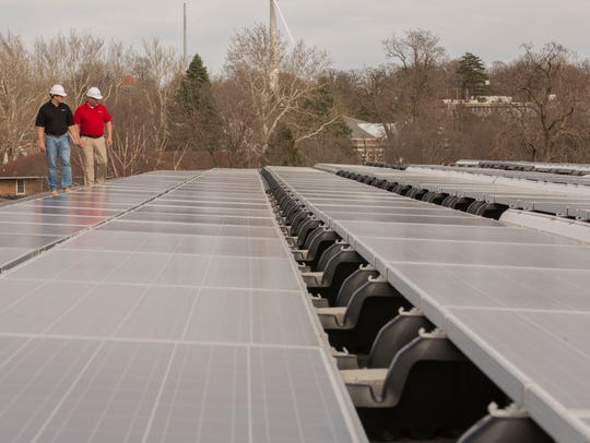 MidAmerican Energy workers check solar panels on the