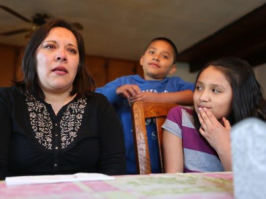 Maria Diaz sits with her son, Oscar, 9, daughter, Miranda,