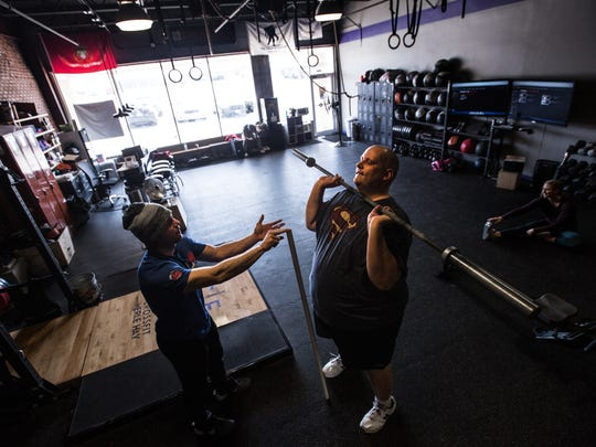 Daniel Finney works with coach Nate Yoho at CrossFit Merle Hay Monday, March 21, 2016.