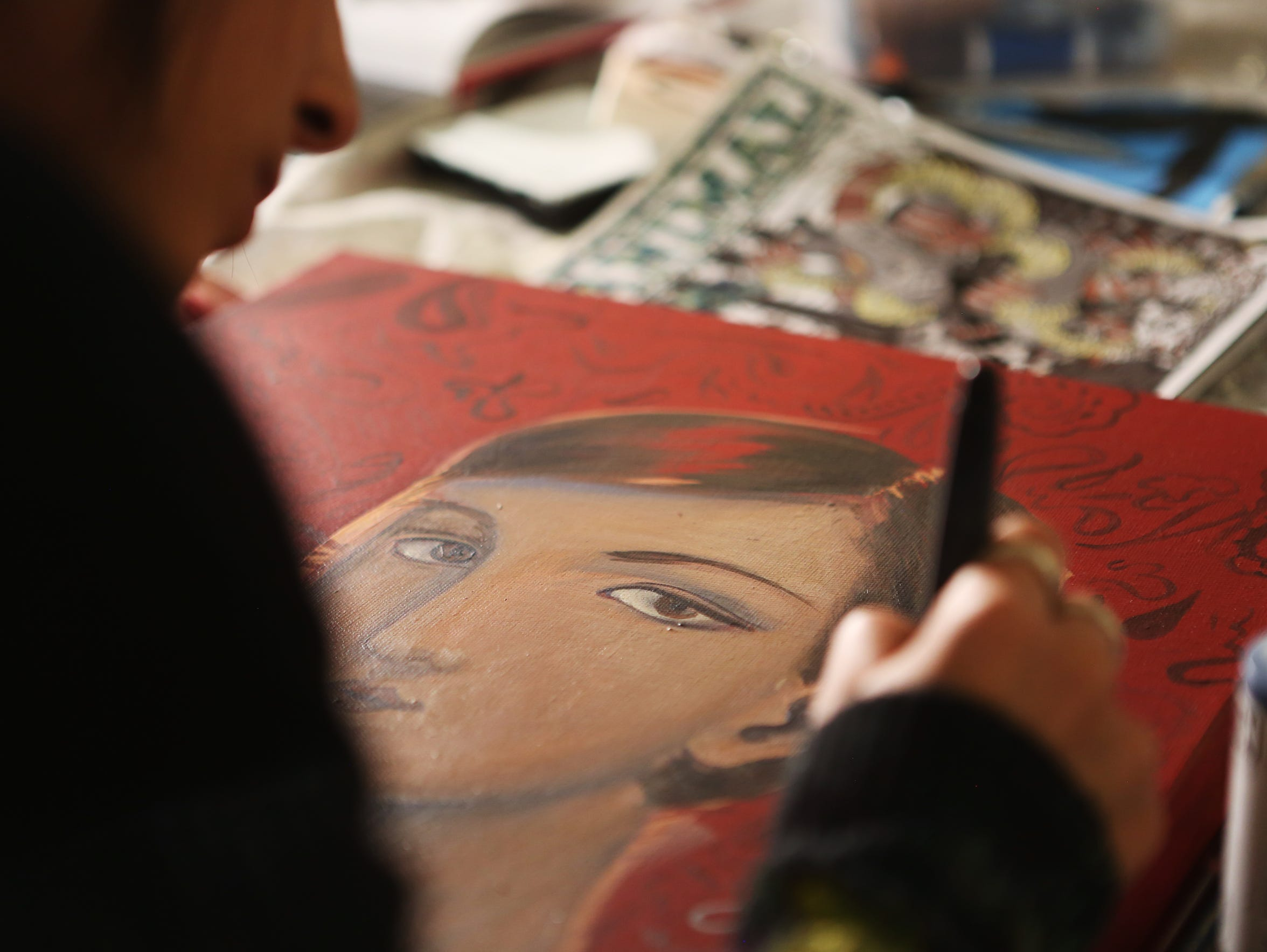 Artist Sofia Enriquez works on a portrait at MAKE in