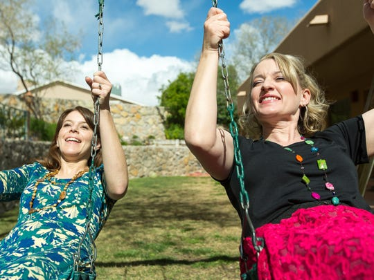 Sisters Bailey Williams, 31, left, and Piper Gibson, 36, swing together in the backyard of Gibson's home.
