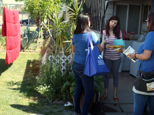 Yesenia Ortiz, and Maribel Cumplido with Clinicas de Salud de Pueblo, talk Laura Zazueta, 30, about Medi-Cal programs newly available to undocumented children on Wednesday, April 13, 2016 at the Fred Young Farm Labor Camp in Indio.