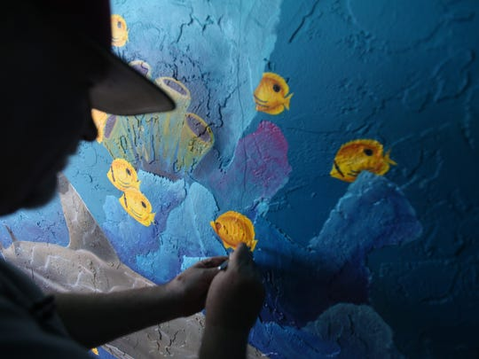 Local artist, Alan Mishagi touches up a mural on the Lani Kai on Fort Myers beach, where he's been painting for 20 years.
