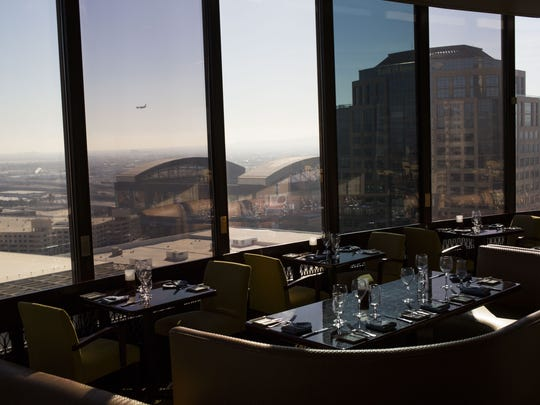 Dinner tables sit vacant before the restaurant opens at the top of the Hyatt Regency on Wednesday, Jan. 20, 2016, at the Hyatt Regency in Phoenix, Ariz.