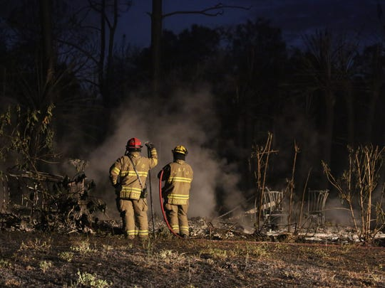 Firefighters work to put out hot spots at what remains of a Lehigh Acres home Wednesday.