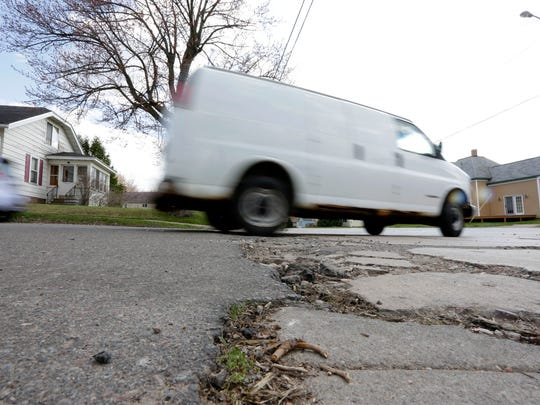 A van rolls by on some recently fixed potholes at the intersection of Maple Avenue and 17th Street in Marshfield on Thursday, April 21, 2016.