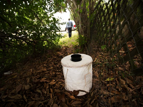 Tom Miller, an employee of the Lee County Mosquito Control leaves a mosquito trap in a neihborhood off of Palm Beach Boulevard near Ortiz Avenue on Wednesday 4/28/2016.  The trap catches the types of mosquitos that could carry the Zika virus.
