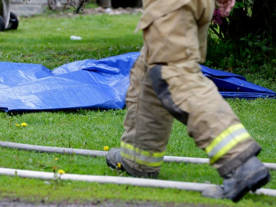 A firefighter walks past the covered body of a 14-year-old black Labrador that perished inside a house fire at 5228 Third Ave. in Pittsville, May 11, 2016.