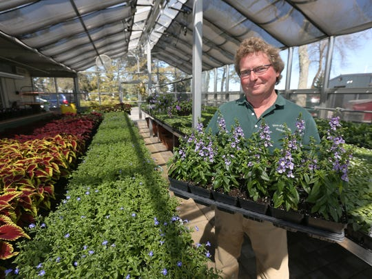 FILE - Don Cisler, head gardener and horticulturist of West of the Lake Gardens, poses for a photo with a tray of angelonia at the greenhouse of the gardens in 2016.