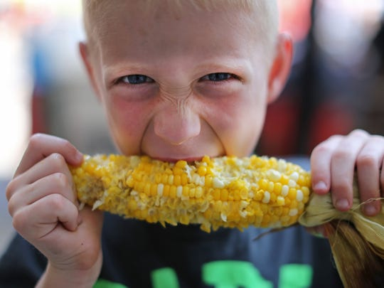 Keagan Leisure of Mason enjoyed an ear of fresh corn from Pit to Plate at Taste of Cincinnati last year.