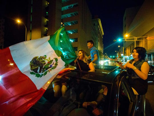 A woman waves the Mexican flag while driving past the Albuquerque Convention Center after a rally by presidential candidate Donald Trump on Tuesday, May 24, 2016.