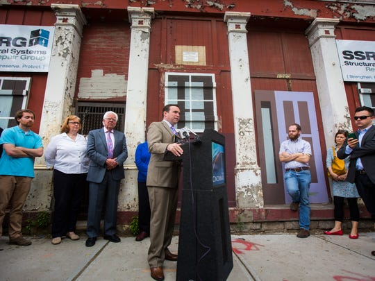 Mayor John Cranley stands in front of buildings where