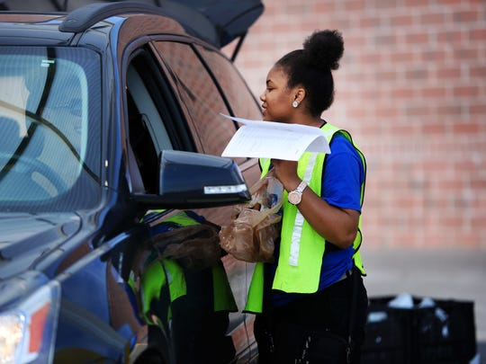Shawncea Colvin, 17, talks with a costumer as she brings