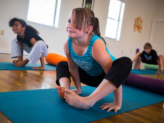 Jasmine Masterson, 9, engages in a yoga pose at Downtown