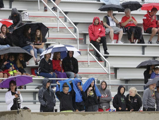 Stevens Point softball fans take cover while their game is under a rain delay during the WIAA Division 1 quarterfinal game against Kenosha Tremper at Goodman Diamond in Madison in June 2016.