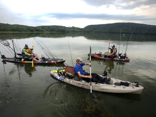 Joe Solari of New City, left, Dallin Swenson of Bardonia, and Devin Rosche of Brooklyn, paddle their kayak's out on to Rockland Lake to cast their lines June 10, 2016. The three fisherman are among a subset of fisherman who use kayak's for fishing. Solari says that among other factors, fishing from a kayak allows him to fish in shallower waters than when fishing in larger boats.