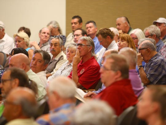People listen to the discussion about raising water