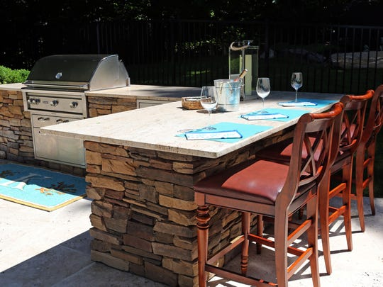 A new trend that home buyers are looking for is having an outdoor oasis that resembles the comfort of the indoors. The outdoor kitchen with upscale appliances, barstools and a granite countertop in a Westchester backyard, June 14, 2016.