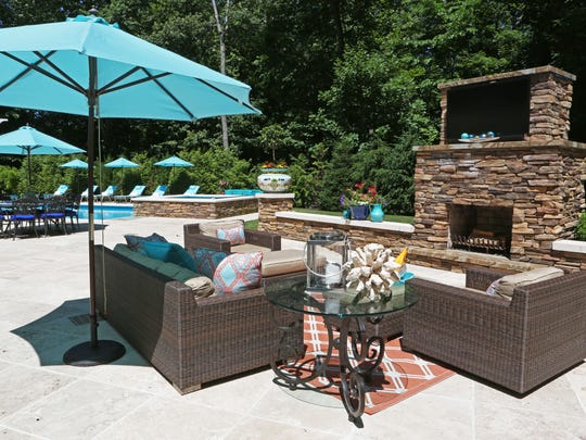 A new trend that home buyers are looking for is having an outdoor oasis that resembles the comfort of the indoors. The outdoor living room with all-weather furniture, fireplace and television in a Westchester backyard, June 14, 2016.