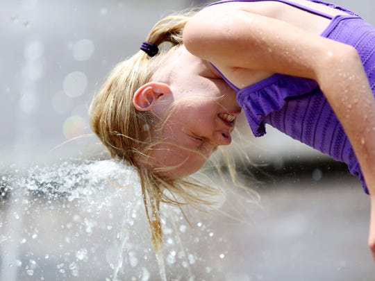 Juliette Welch, 9, cools off her head in the water fountains at Spring Canyon Park Monday, July 22, 2014.