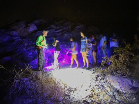 Participants in a night hike led by Friends of the Desert Mountains walk the Art Smith Trail with backlights to spot scorpions on Saturday, June 25, 2016.