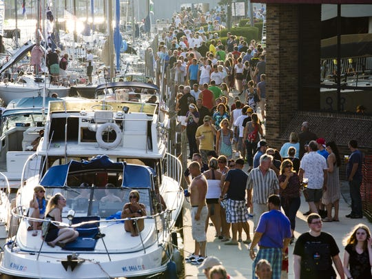 Hundreds of people walk along the river walk by the Zebra Bar during Boat Night July 17, 2015, on the Black River in Port Huron.