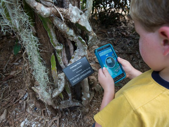 Ben Moore, 5, of Virginia Beach, compares signs to find the right Pokestop at the Naples Zoo on July 15, 2016 in Naples, Florida. Zoo volunteers placed Pokemon Go lures throughout the Zoo from 10 am to 4 pm so visitors could play at a Pokemon gym, 15 Pokestops and other locations throughout the park.