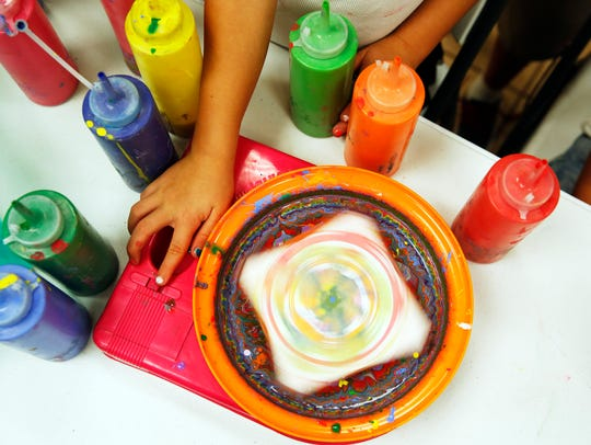 Children take turns painting using a spinning wheel