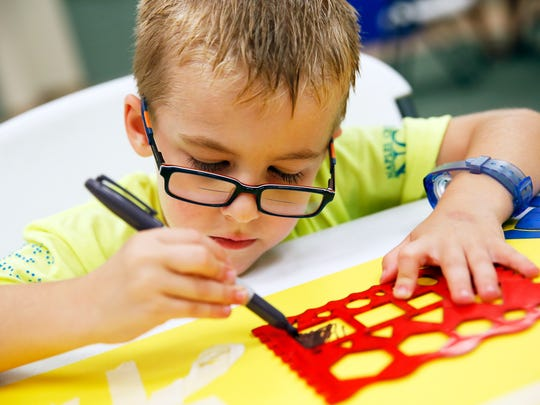 Andrew Muller, 5, of Naples colors using stencils during