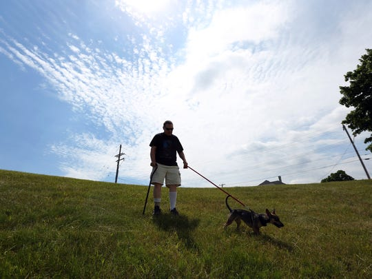 Charles Hagen lets Murphy leading him walking down a hill at Washington Park on Thursday, June 30 in Two Rivers. Murphy goes to everywhere with Hagen and she has been able to pull Hagen out of a situation that would trigger his anxiety.