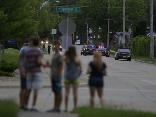 Onlookers watch police activity near Spencer and Outagamie streets on Saturday, July 23, 2016 in Appleton, Wis.