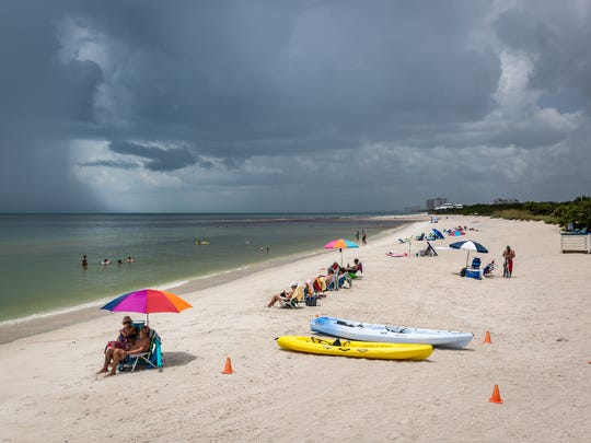 Beachgoers soak up the sun and a few rain showers near