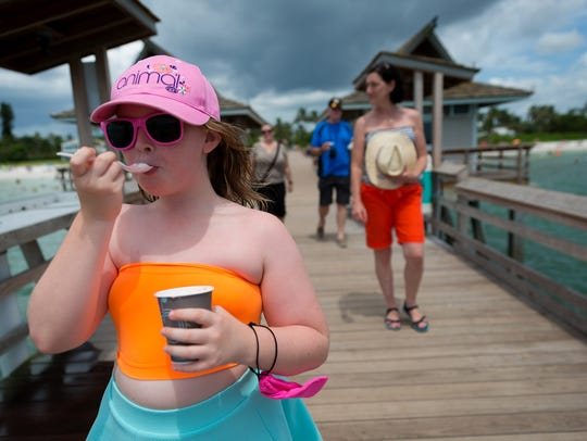Eight-year-old Lucy Varker eats ice cream while visiting