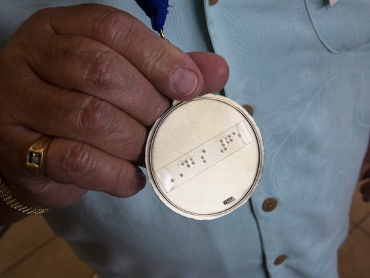 Bruce Miles displays the medal, which reads DBS #75 in Braille, that he received during the 75th Anniversary celebration of the Division of Blind Services on July 28, 2016 in Fort Myers, Florida.